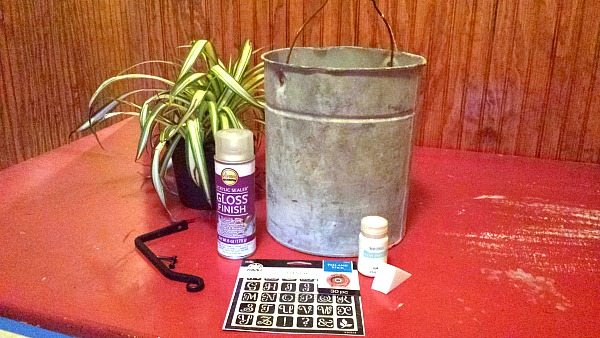 An old bucket with a plant and the supplies to create a stenciled planter.