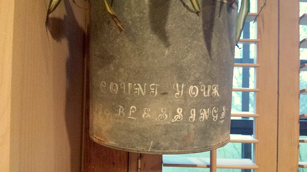 "An old metal bucket stenciled with the words ""Count Your Blessings""."