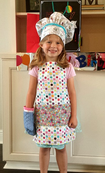 A little girl in her chef outfit.