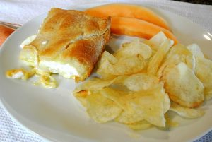 Crescent rolls, cream cheese, three types of cheese, butter, and an egg is what is in this delicious dish.