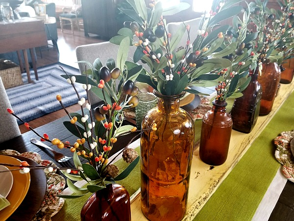 fall centerpiece with amber glass bottles